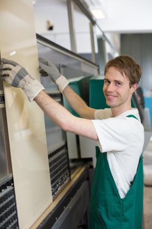 glasscutter: Worker in glaziers workshop putting glass in grinding machine