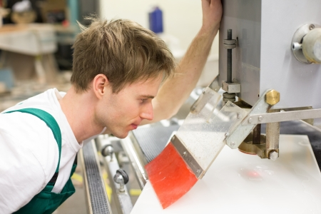 glasscutter: Worker in glaziers workshop operating a glass drilling or milling machine