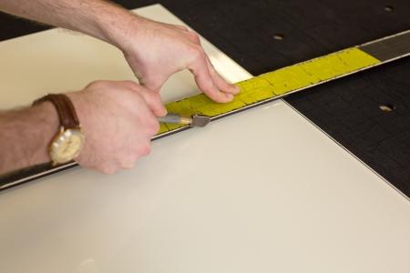 glasscutter: Worker cutting glass in glaziers workshop