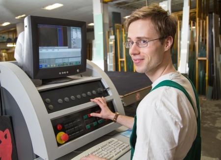 glasscutter: worker in glaziers workshop operating a cutting machine