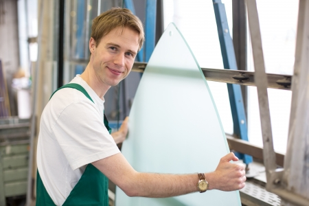 glazier: Glazier handling a piece of glass in workshop Stock Photo