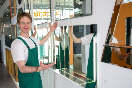 glasscutter: Glazier presenting mirrors and different types of glass in showroom