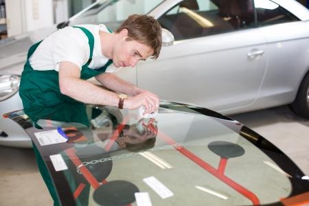 window repair: Glazier handling car windshield or windscreen made of glass in garage Stock Photo