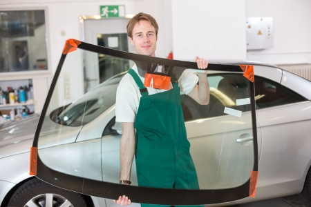 window repair: Glazier handling car windshield or windscreen made of glass in garage Stock Photo