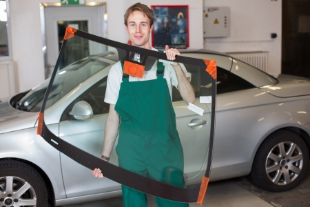 Glazier handling car windshield or windscreen made of glass in garage photo