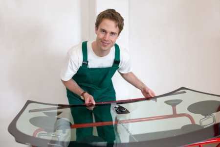 glazier: Glazier preparing sealing for car windshield