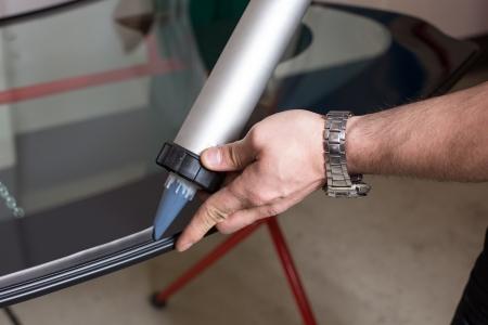 glasscutter: Glazier applying rubber sealing to windshield in garage