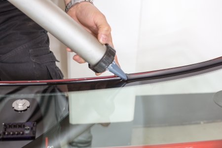 Glazier applying rubber sealing to windshield in garage