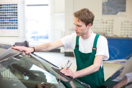 car manufacturing: Glazier installs windscreen into car in garage Stock Photo