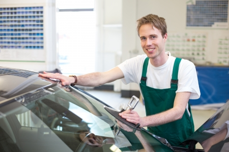 car glass: Glazier installs windscreen into car in garage Stock Photo