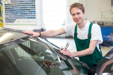 glazier: Glazier installs windscreen into car in garage Stock Photo