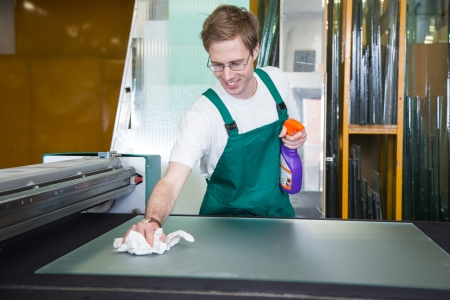 glazier: glazier in workshop cleaning a glass