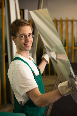 glasscutter: Worker in glaziers workshop or glass warehouse handling glass Stock Photo