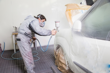 Car body painter spraying paint or color on bodywork in a garage or workshop with an airbrush Stock Photo