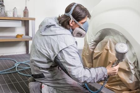 Karosserie Maler Sprühfarbe oder Farbe auf Karosserie in einer Garage oder Werkstatt mit einer Airbrush