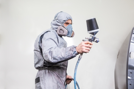 paint gun: Car body painter spraying paint or color on bodywork in a garage or workshop with an airbrush Stock Photo