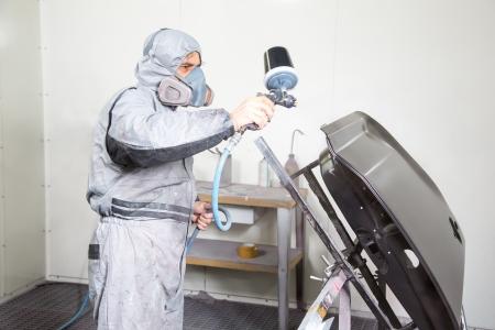 hombre pintando: Pintor de carrocer?de coche pulverizaci?e pintura o el color de la carrocer?en un garaje o taller con un aer?fo Foto de archivo
