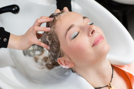 beauty saloon: hairdresser washing customers hair in salon