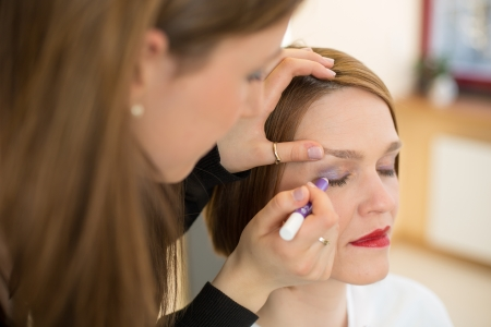 Cosmetician applying eye shadow to customer Stock Photo
