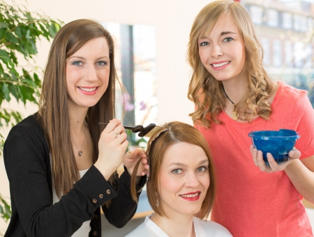 hair coloring: hairstylists or hairdresser dying hair of customer with color paint Stock Photo