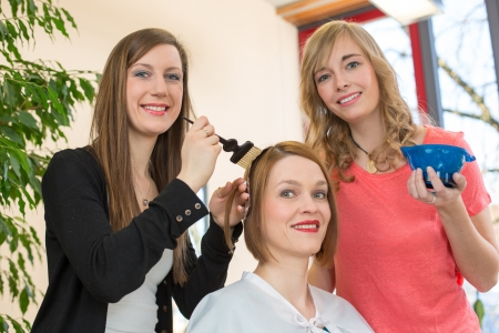 hairstylists or hairdresser dying hair of customer with color paint photo