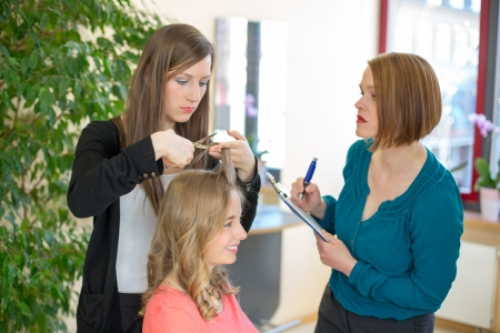 hairdresser apprentice cutting hair while instructor is watching