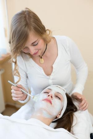 masajes faciales: Cosmetician que aplica la m�scara facial para cuidado de la piel del cliente