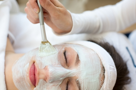 Cosmetician applying facial skincare mask to customer photo