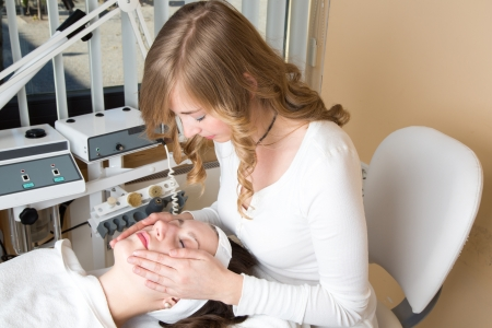 Cosmetician giving client a facial massage photo
