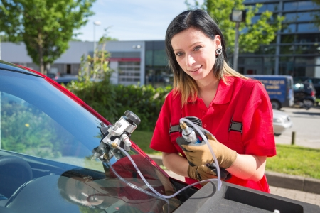 glazier: Glazier repairing windshield on a car after stone-chipping damage