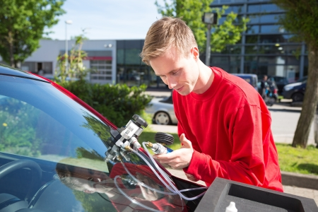 Glazier repairing windshield on a car after stone-chipping damage