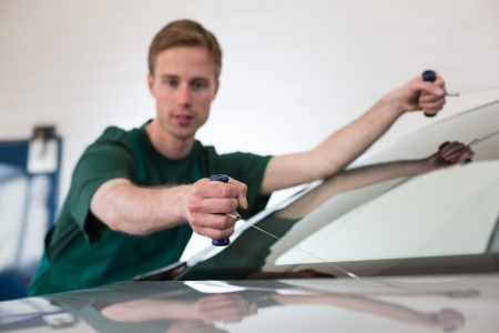 Glazier cutting adhesive of windscreen with a wire to replace windshield photo