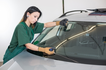 stone cutter: Glazier cutting adhesive of windscreen with a wire to replace windshield