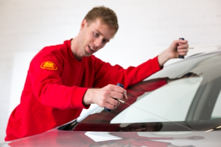 glazier: Glazier cutting adhesive of windscreen with a wire to replace windshield