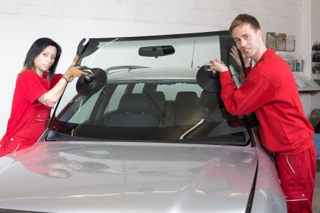 replacements: Glazier removing windshield or windscreen on a car