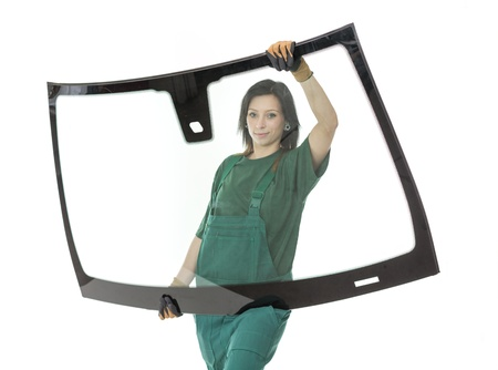 Worker glaziers workshop with car windscreen or windshield isolated in front of white background photo