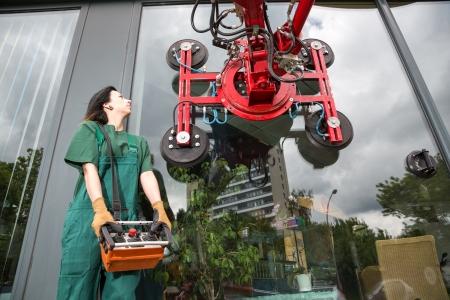 glasscutter: Glaziers operating a glass installation crane at glaziers workshop Editorial