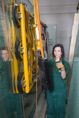 glazier: Glazier in glass storage or warehouse operating a crane Stock Photo