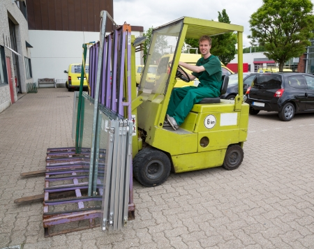 glazier: Glazier operating a forklift truck loaded with panes of glass Editorial