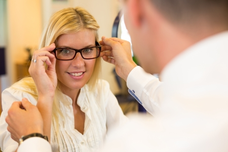 Optician or optometrist consulting a customer about eyeglasses, spectacles and frames in a shop photo