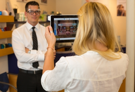 Optician or optometrist measuring the eye distance of a customer with a tablet computer photo