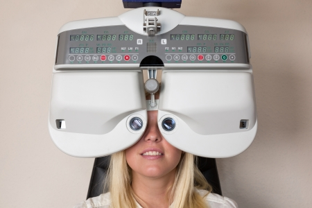 Customer of a optometrist or optician looking through phoropter to determine the right glasses Standard-Bild