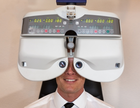farsighted: Customer of a optometrist or optician looking through phoropter to determine the right glasses Stock Photo