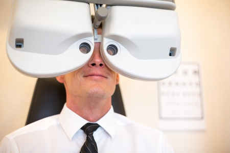 determine: Customer of a optometrist or optician looking through phoropter to determine the right glasses Stock Photo