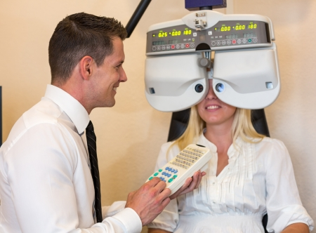 Optician or optometrist consulting a customer who is looking through a phoropter photo