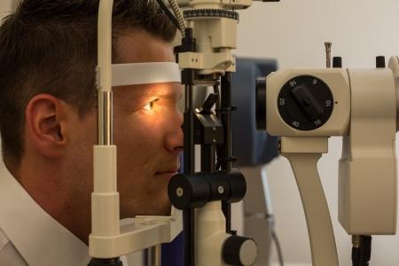 slit: Paciente o cliente en la l?mpara de hendidura en optometrista u ?ptico
