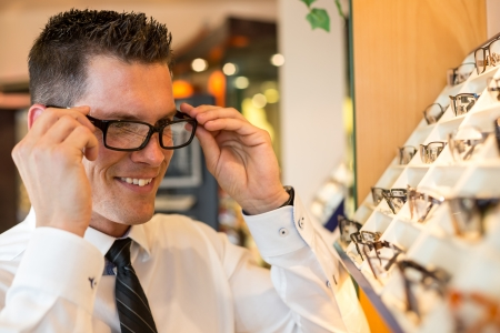farsighted: Customer in opticians shop choosing the right frame for eyeglasses from a shelf with many different models
