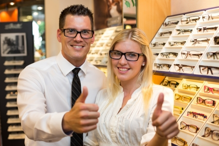 Customers in opticians shop choosing the right frame for eyeglasses from a shelf with many different models and showing thumbs up