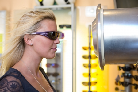 whether: Customer testing whether sport eyeglasses are windproof in front of wind tunnel in opticians shop Stock Photo