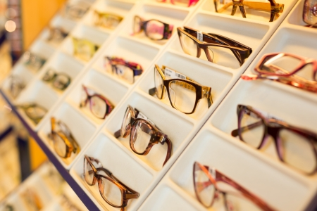 Eyeglasses, shades and sunglasses in opticians shop Stock Photo
